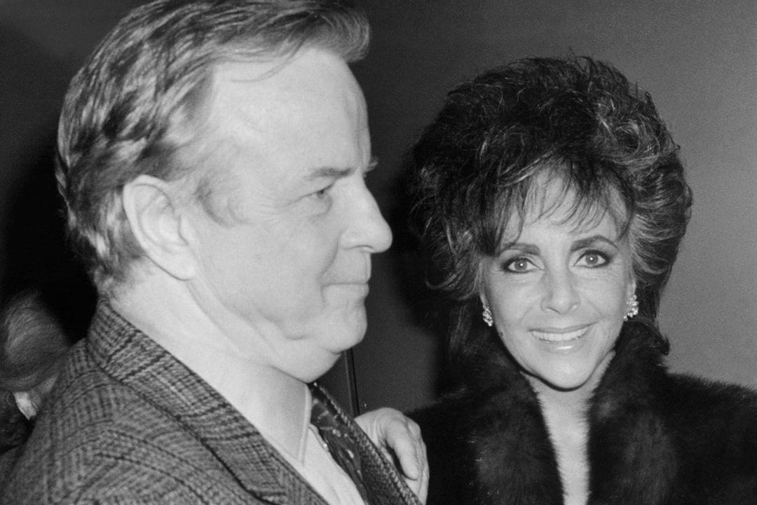 """Franco Zefferelli, produtor e cenógrafo da ópera Puccini """"Turandot"""", acompanha Liz Taylor para sua limusine após a apresentação em 1987."""