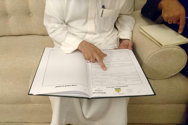 O clérigo saudita Abdulmohsen al Ajemi mostra exemplos de contratos matrimoniais, em Riade, em 19 de junho de 2019