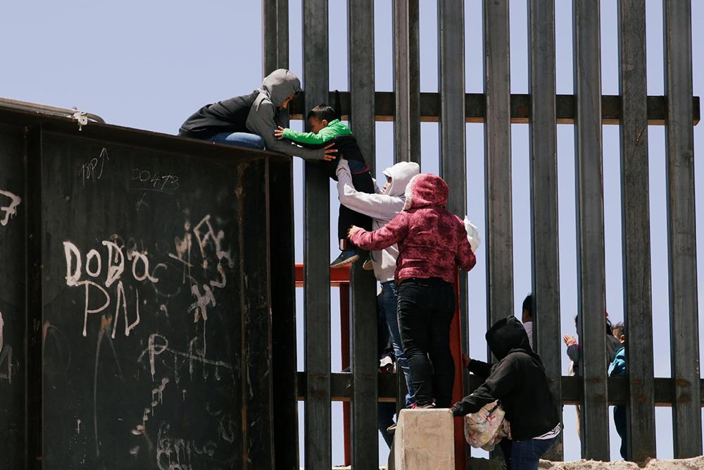 22.jun.2019 - Migrantes pulam sobre muro para cruzar a fronteira dos EUA com o México em Ciudad Juarez.