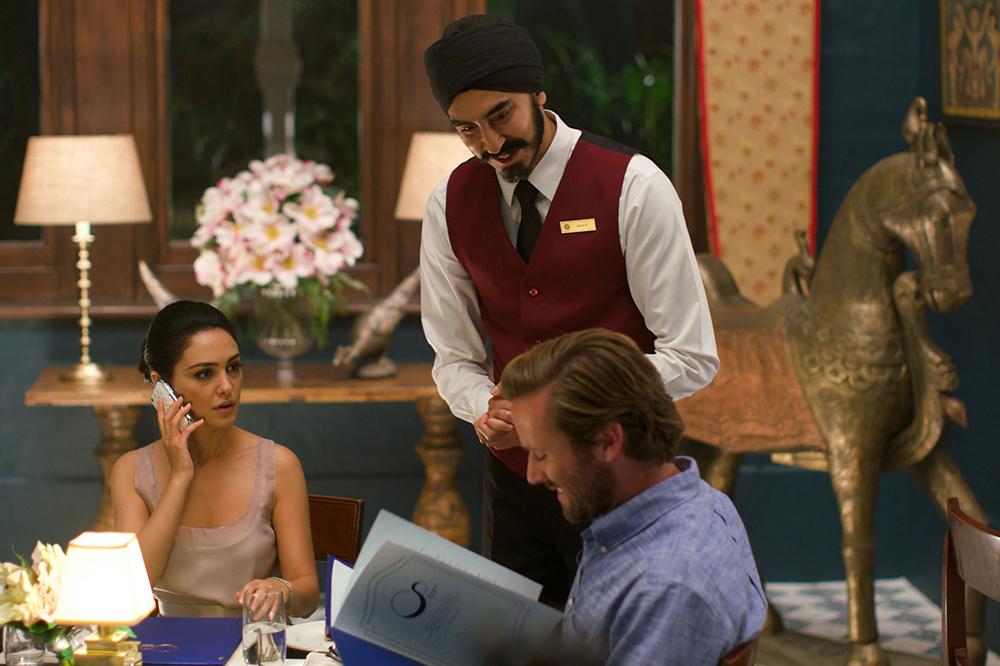 O garçom Arjun (Dev Patel) escolheu arriscar-se pelo hóspedes, dentre eles o casal David e Zahara (Armie Hammer e Nazanin Boniadi).