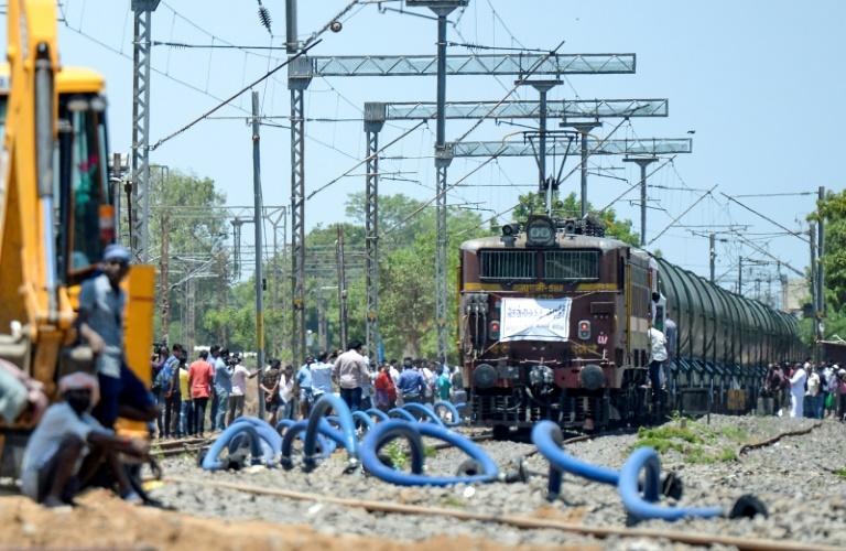 Moradores indianos se aglomeram em torno de trem especial de 50 vagões carregados com litros de água, na estação de Villivakkam, na cidade de Chennai, em 12 de julho de 2019.