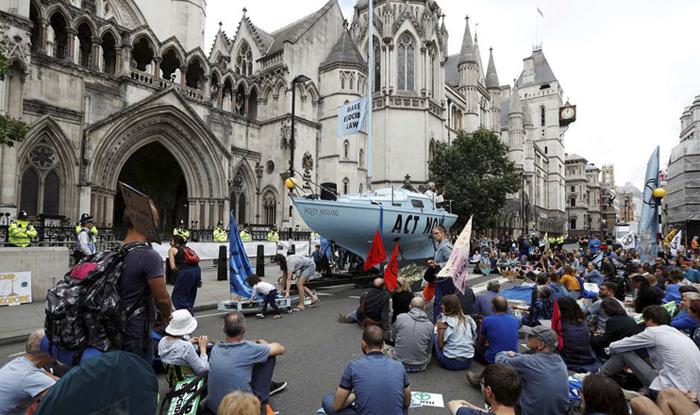 Ativistas posicionaram um barco azul diante dos Tribunais Reais de Justiça, no centro londrino, e se sentaram na rua fazendo ioga.