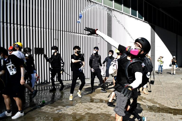 Manifestante lança garrafa d'água contra a polícia em Hong Kong.