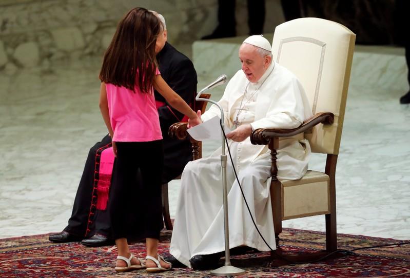A menina, que usava uma camiseta rosa com a palavra 'Amor', se aproximou do papa.