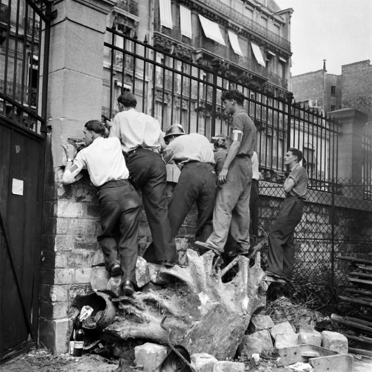 Membros das FFI (Forças Francesas do Interior) se protegendo atrás de uma parede em Paris, ainda ocupada.