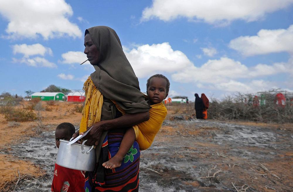 A fome é a face oculta e silenciosa do capitalismo. Na foto, mãe com dois filhos anda até um centro de distribuição de comida na Somália em 2017.