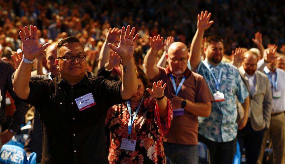 Membros da Convenção Batista do Sul e convidados erguem as mãos em oração durante a reunião anual da convenção em Birmingham, Alabama.
