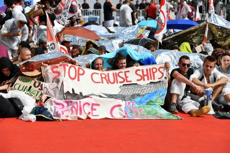 Manifestantes erguem cartazes contra os navios de cruzeiro que navegam na lagoa de Veneza e a mudança climática, no acesso ao tapete vermelho do Palácio de Cinema (Palazzo del Cinema), durante o 76º festival de cinema de Veneza.