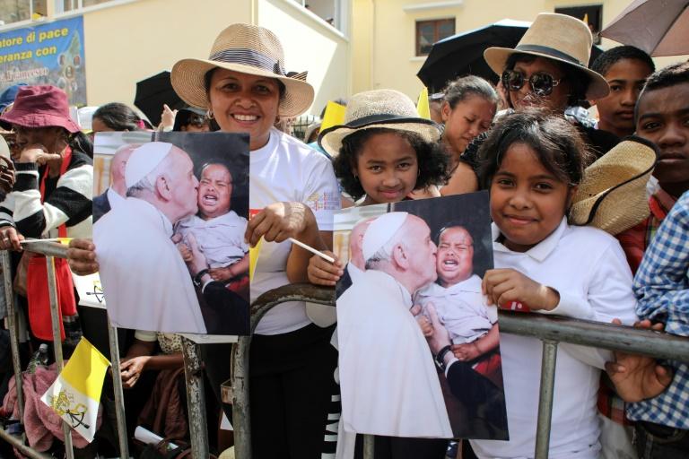 Fiéis cumprimentam a passagem do Papa Francisco por uma rua em Antananarivo
