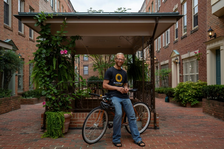 Tarek Maassarani, que adotou um estilo de vida de controle de suas pegadas de carbono, posa com sua bicicleta de mais de uma década na garagem do prédio de um amigo em Washington
