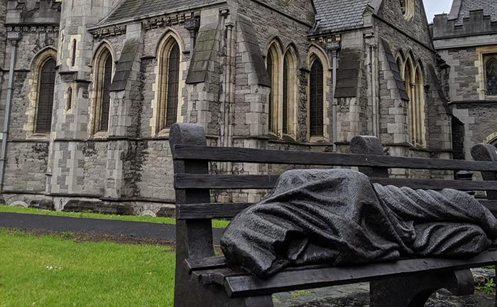 Estátua do lado de fora da Catedral de Dublin, Irlanda. Ela descreve Jesus como um sem-teto dormindo em um banco fora da igreja e serve como um lembrete de que ele se identificou com os pobres e marginalizados.