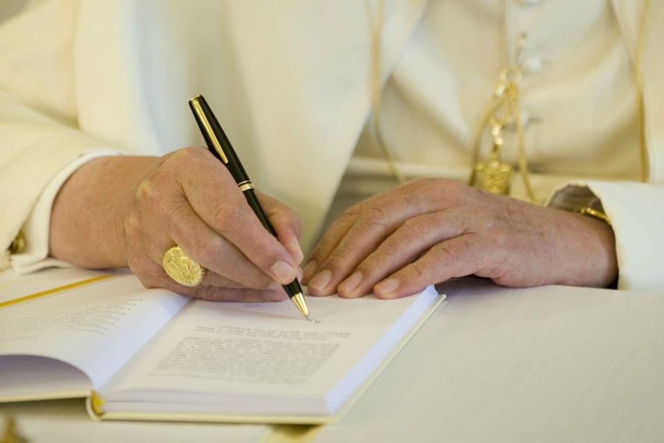 O papa Bento XVI assina uma cópia de sua encíclica 'Caritas in Veritate', no Vaticano em 6 de julho de 2009, que aborda a crise econômica global.