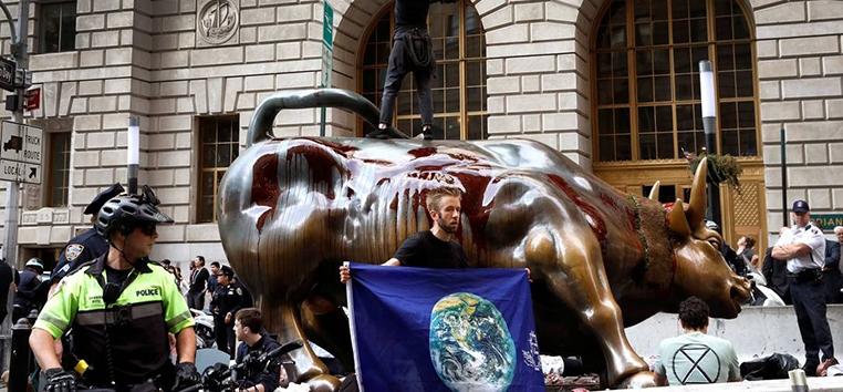 Ativistas pelo clima do grupo Extinction Rebellion protestam em Nova York, com sangue falso no touro de Wall Street. (Mike Segar/Reuters)