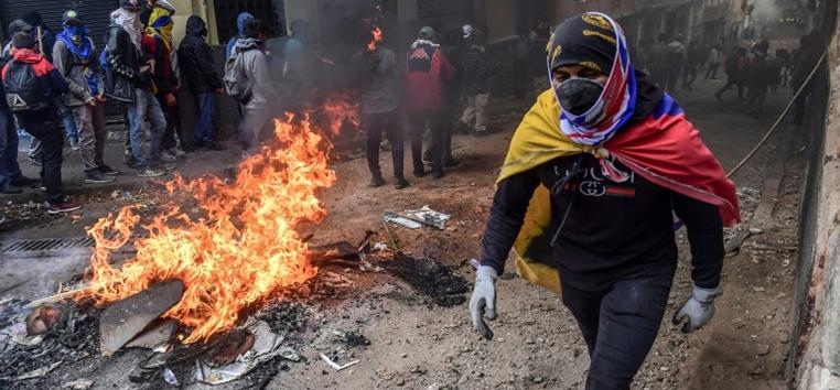 Manifestante passa por barricada durante protestos em Quito na quarta-feira (9). (AFP)