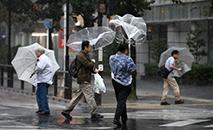 Peatones en el centro de Tokio el 12 de octubre de 2019, antes de la llegada del tifón Hagibis (AFP)
