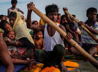 Refugiados rohingya cruzam o rio Naf com uma jangada improvisada. (Mohammad Ponir Hossain/Reuters)