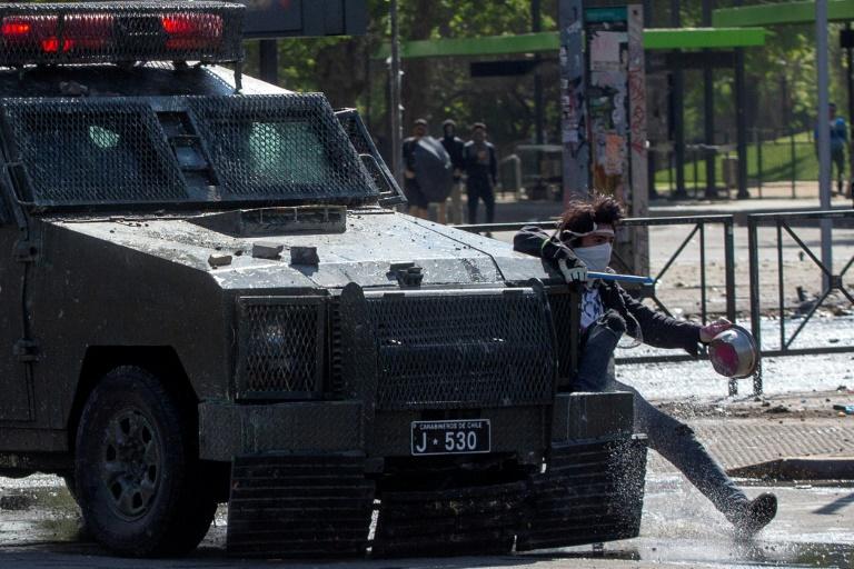 Manifestante se agarra a um veículo do Batalhão de Choque durante confronto em Santiago