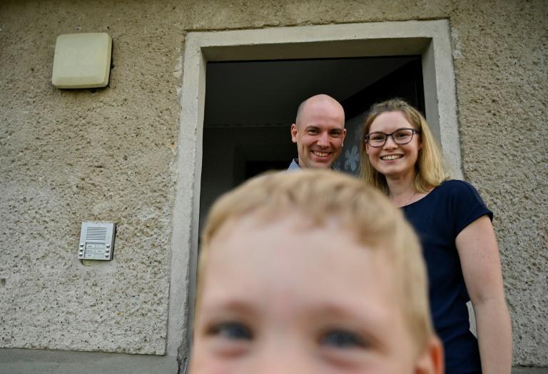 Carsten e Peggy Hoffmann posam com um de seus dois filhos em frente a sua casa em Glindenberg, Alemanha