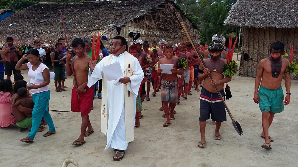 Pe. Justino Sarmento em procissão com comunidade indígena na Amazônia.