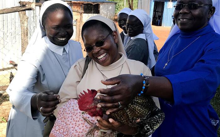 Irmãs do Quênia cuidam de galinhas enquanto aprendem sobre as oportunidades de empreendimentos sociais em uma fazenda de aves.