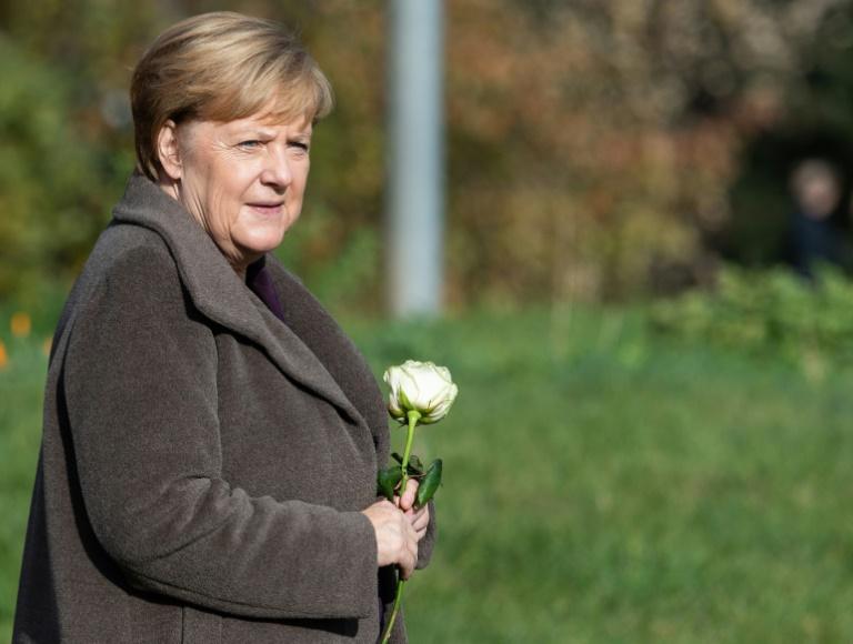 A chanceler alemã Angela Merkel segura uma rosa na árvore memorial em homenagem a uma vítima da NSU