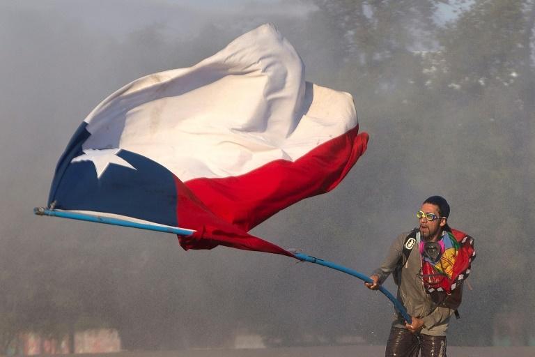 Manifestante segura a bandeira do Chile durante confronto