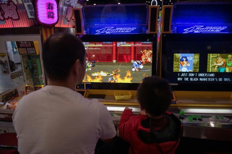 Uma criança e um adulto se divertem com um videogame em uma loja em um shopping center em Pequim
