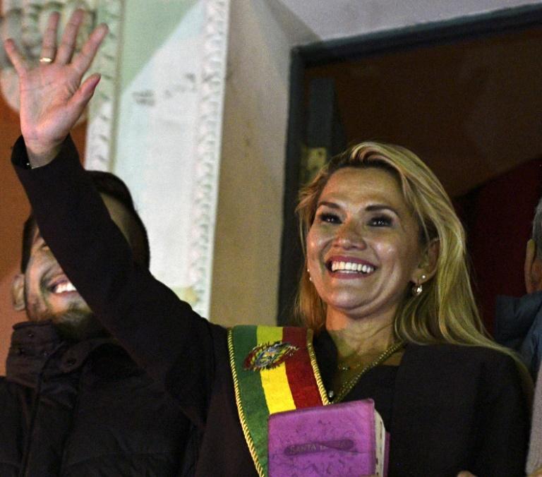 A senadora Jeanine Añez acena para a multidão como presidente interina da Bolívia, em 12 de novembro de 2019, em La Paz