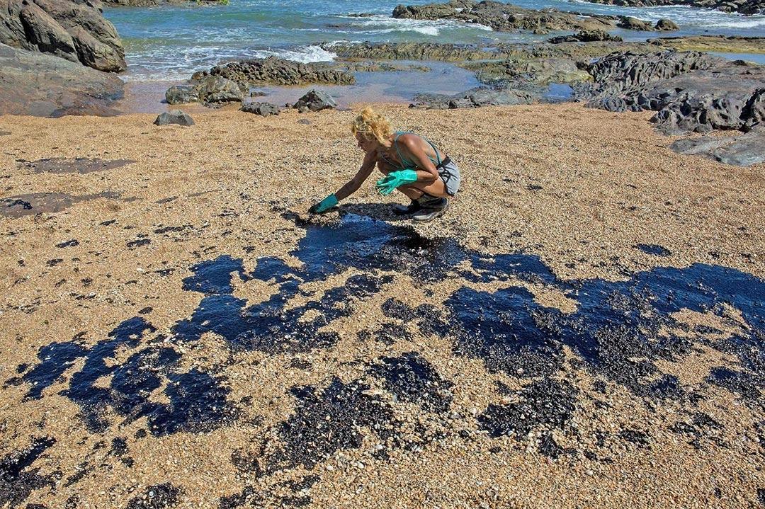 Em Lauro de Freitas (BA), voluntária retira resíduos de óleo na praia