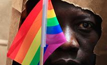 Homem de Uganda cobre rosto para proteger identidade em parada gay em Boston. (Reuters)