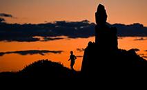 """Um homem corre ao lado do monumento """"Le Bateau Ivre"""" (o navio bêbado) Adam quando o sol se põe sobre o mar Mediterrâneo, perto da praia do Prado em Marselha, sul da França. (AFP)"""