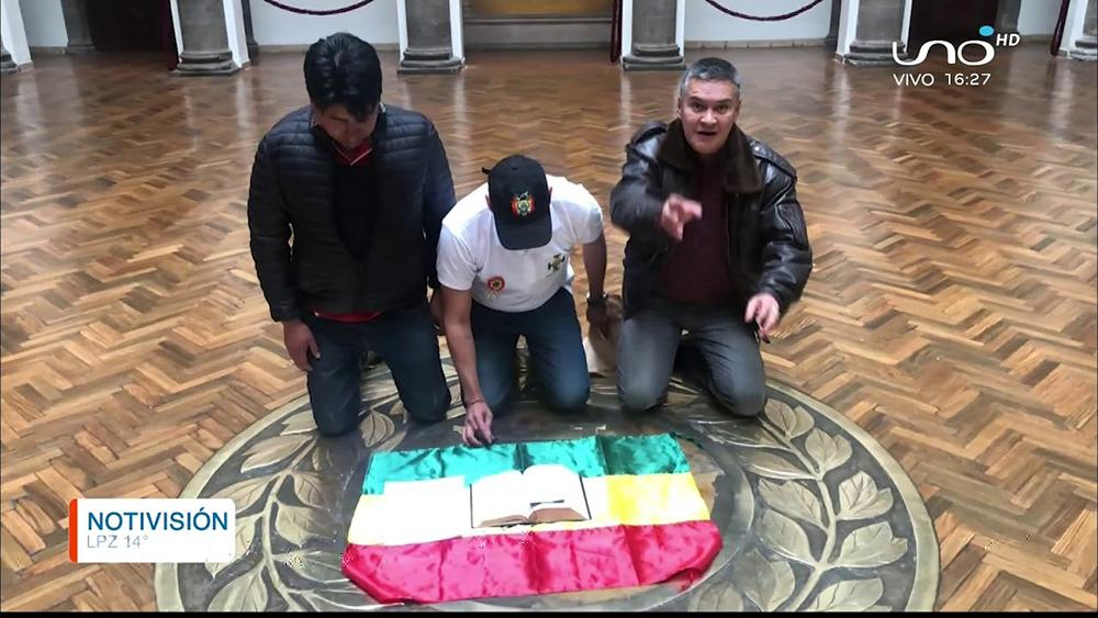 Diante de uma bíblia, o líder opositor Luis Fernando Camacho (ao centro) se ajoelhou no Palácio Quemado