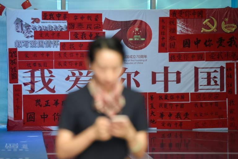Mulher usa celular, diante do cartaz do 70º aniversário da fundação da República Popular da China