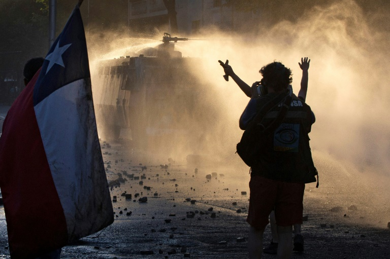 Manifestantes chilenos desafiam a polícia durante protesto em Santiago, em 29 de novembro de 2019.