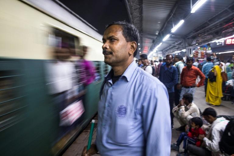 O cego Vinod Kumar Sharma aguarda em uma plataforma na estação Hazrat Nizamuddine, em Nova Délhi, o trem para voltar para casa depois do trabalho