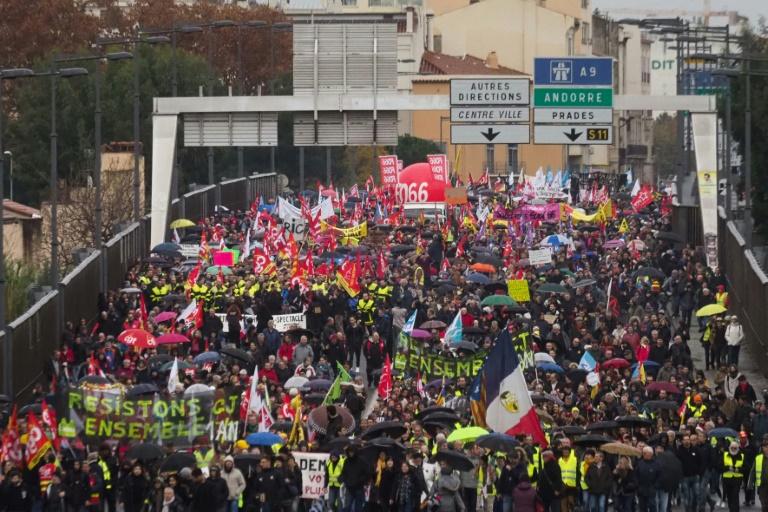 Pessoas segurando bandeiras e estandartes participam de uma manifestação para protestar contra a reforma da previdência, em Perpignan, sul da França