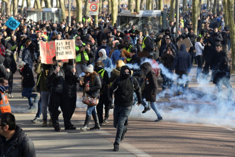 Manifestantes correm para se proteger de bombas de gás lacrimogênio durante protesto contra reforma previdenciária em Bordeaux, França