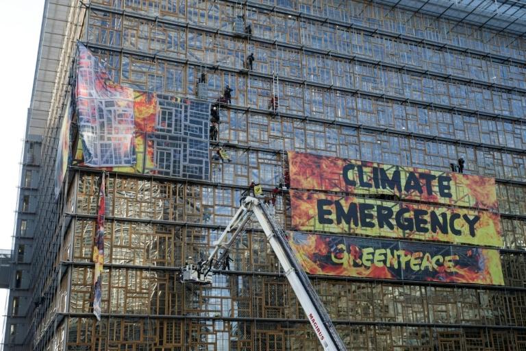 Bombeiros evacuam ativistas do Greenpeace que penduraram o grande banner com o slogan 'Emergência climática' na fachada do prédio do Conselho Europeu, em Bruxelas