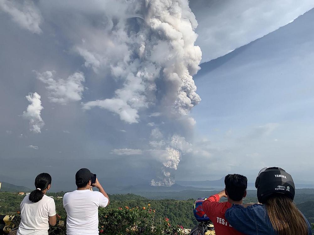 Pessoas tiram fotos de uma explosão freática do vulcão Taal, nas Filipinas