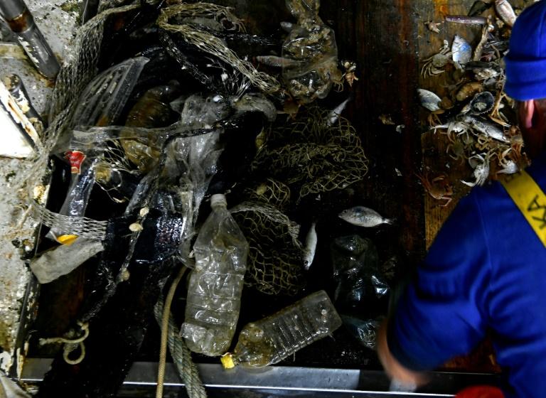 Pescador recolhe o lixo em sua rede, na costa de San Benedetto del Tronto, na Itália, em 22 de maio de 2019