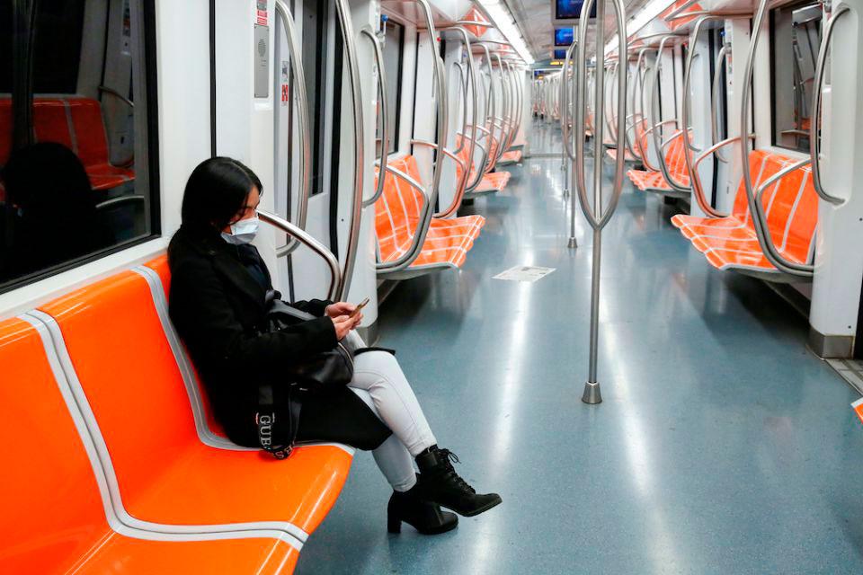 Uma mulher usando uma máscara de proteção contra o coronavírus senta-se dentro de um trem de metrô vazio em Roma, 12 de março