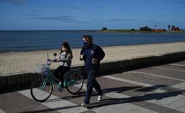 Um homem e sua filha, ambos com máscaras, se exercitam em Montevidéu, Uruguai (Arquivos/AFP)