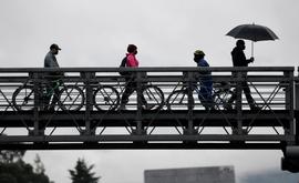 Pessoas atravessam de bicicleta uma ponte para pedestres em Bogotá (AFP)