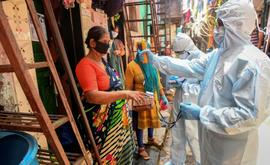 Profissionais de saúde realizam inspeção de porta em porta em Dharavi (AFP)