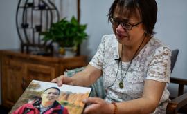 Zhong Hanneng mostra uma foto do filho, que morreu vítima de covid-19, em um encontro em Wuhan, China, em 6 de setembro de 2020 (Hector Retamal/AFP)