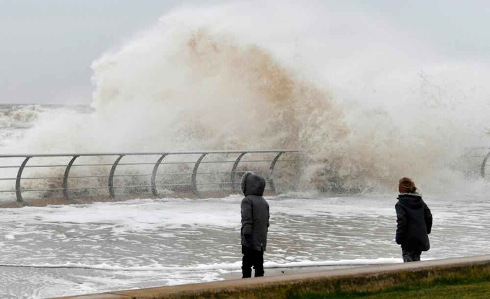 Crianças brincam de pé perto do paredão do mar com ondas no calçadão de Blackpool, no norte da Inglaterra
