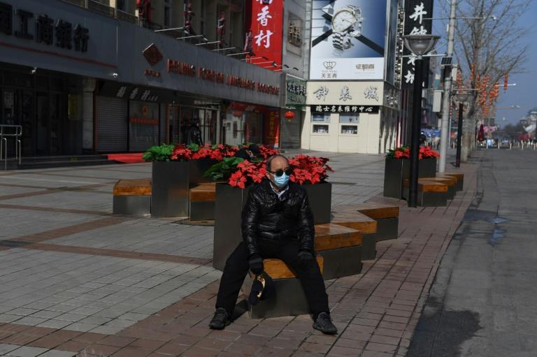 Homem em rua deserta no distrito de Wangfujing, em Pequim: governo recomenta trabalhar de casa