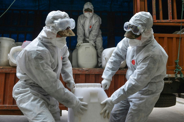 Policiais chineses com trajes de proteção transportam desinfetante na província de Hubei, epicentro da epidemia COVID-19