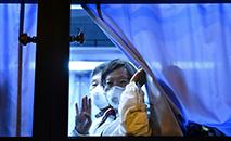 """Passageiro americano retirado do cruzeiro """"Diamond Princess"""" acena para a imprensa ao chegar ao aeroporto de Haneda, em Tóquio (AFP)"""