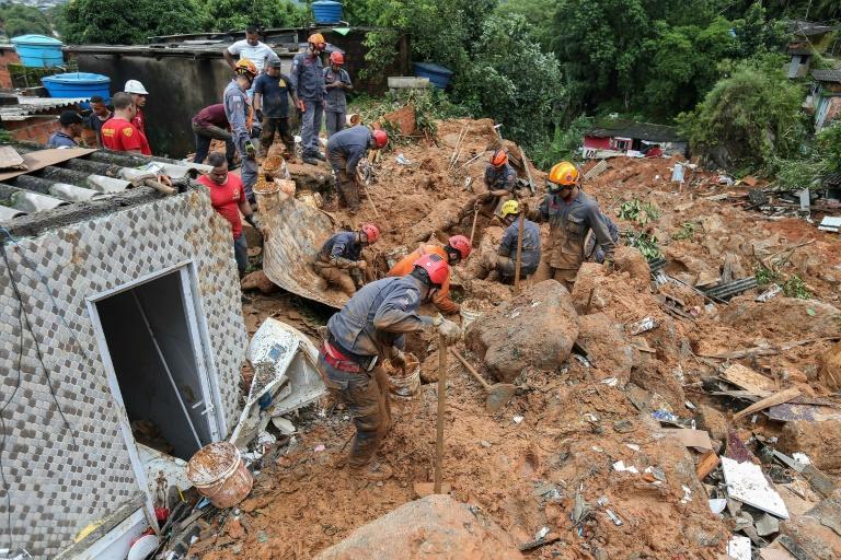 Equipes de resgate buscam vítimas após um deslizamento de terra no Morro do Macaco Molhado, no Guarujá